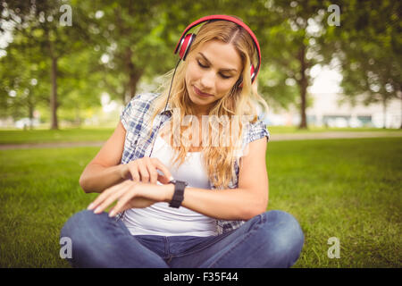 Woman listening to music and using smartwatch at park - Stock Photo