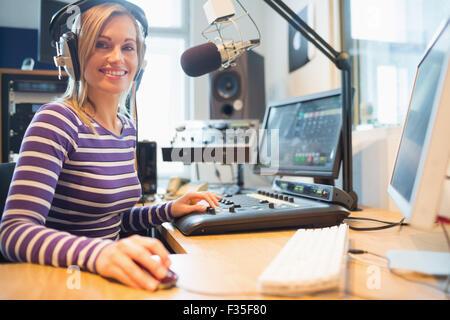 Portrait of female radio host using computer in studio - Stock Photo