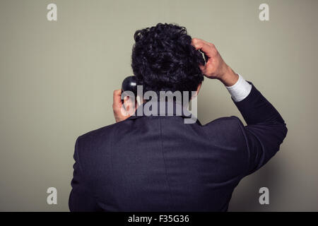 Rear view of a confused businessman on the phone scratching his head - Stock Photo
