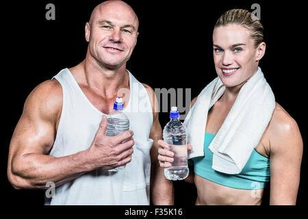 Portrait of confident athlete man and woman with water bottle - Stock Photo