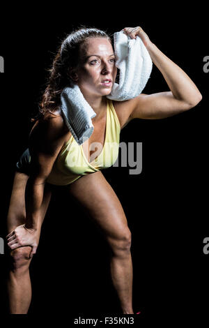 Athlete wiping sweat with towel while looking up - Stock Photo
