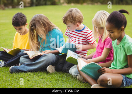 classmates sitting in grass and reading books stock photo royalty