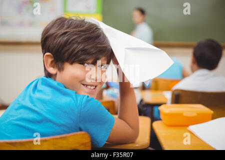 Pupil about to throw paper airplane - Stock Photo