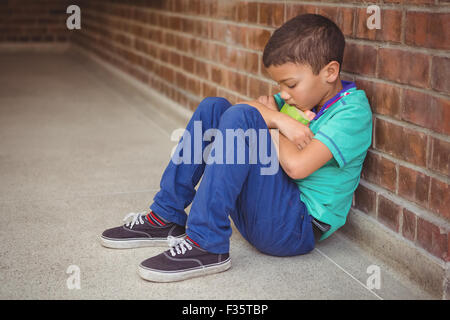 Upset lonely child sitting by himself - Stock Photo