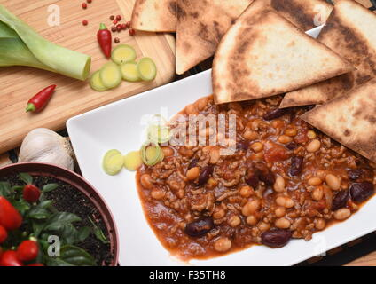Chilli con carne with pepper, garlics and tortillas - Stock Photo