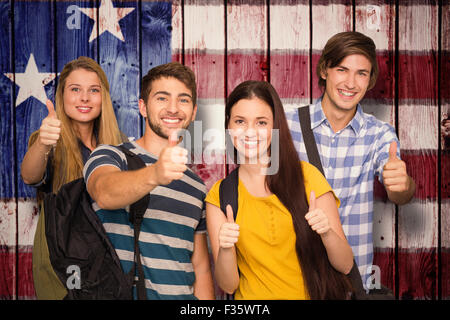 Composite image of happy students gesturing thumbs up at college corridor - Stock Photo