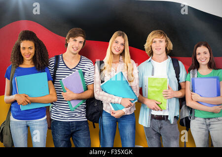 Composite image of happy college students holding folders - Stock Photo
