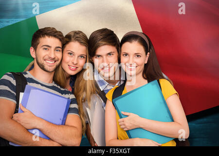 Composite image of happy students holding folders at college corridor - Stock Photo