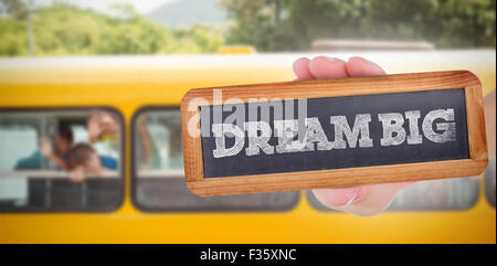 Dream big against cute pupils smiling at camera in the school bus - Stock Photo
