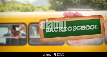 Back to school against cute pupils smiling at camera in the school bus - Stock Photo