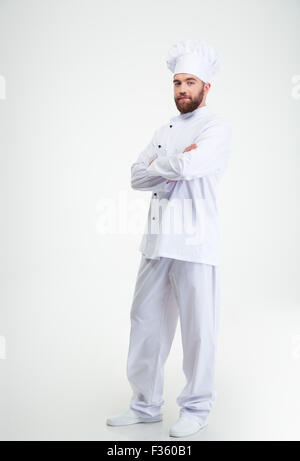 Full length portrait of a happy male chef cook standing with crossed hands isolated on a white background - Stock Photo