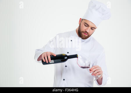 Portrait of a male chef cook pouring wine in wineglass isolated on a white background - Stock Photo