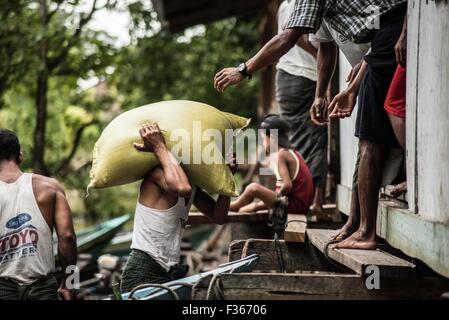 Humanitarian aid supplies are delivered by an NGO to flood hit communities in Myanmar's Irrawaddy delta region. - Stock Photo