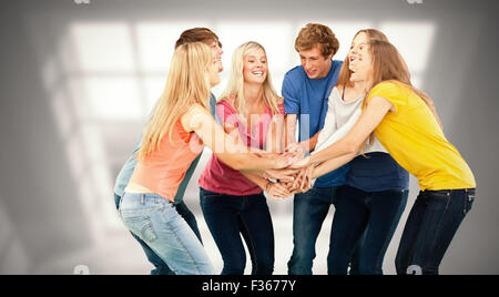 Composite image of group of friends about to cheer with their hands stacked - Stock Photo