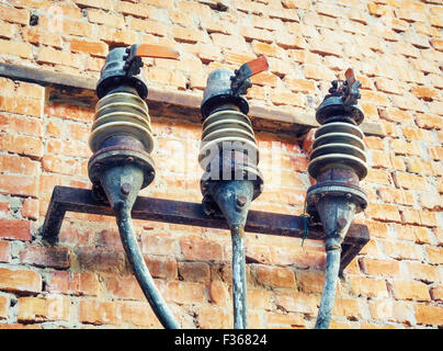 Old fuses on the wall of the brick building. - Stock Photo