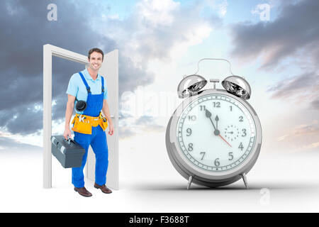 Composite image of happy plumber carrying tool box - Stock Photo