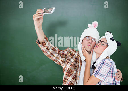Composite image of geeky hipster couple taking selfie with smart phone - Stock Photo