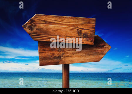 Direction signpost on seaside beach, rustic wooden blank sign in summer vacation resort - Stock Photo