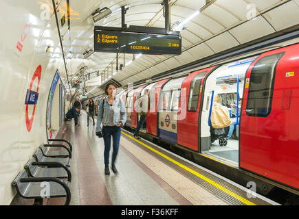 Commuters after getting off a stationary tube train at a London underground station platform London England UK Gb - Stock Photo
