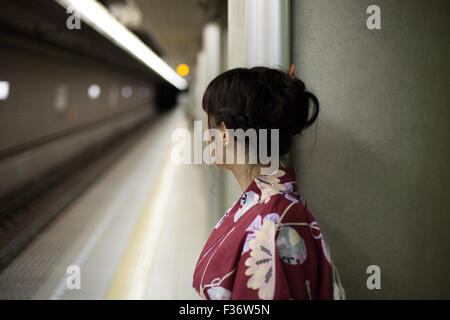 Girl in kimono waiting on subway platform - Stock Photo