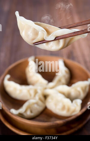 Fresh dumplings with wood chopstick. Popular Chinese food on rustic old vintage wooden background. - Stock Photo