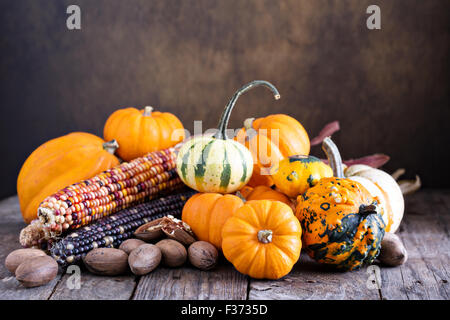 Pumpkins, indian corn and variety of squash on a rustic table - Stock Photo