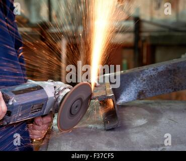 Man using an angle grinder to cut and shape mild steel, Aldridge, West Midlands, UK, Western Europe. - Stock Photo