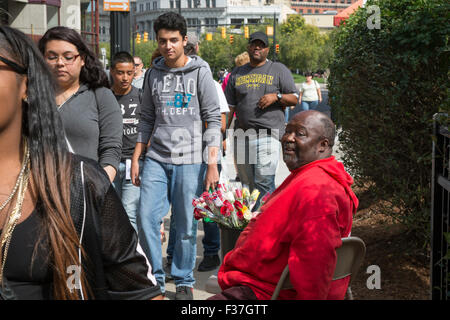 Grand Rapids, Michigan - A man sells flowers on a downtown street as young people walk by. - Stock Photo