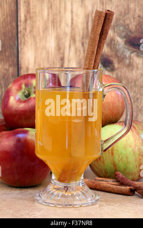 Close up glass of apple cider with cinnamon sticks.  Apples in the background. - Stock Photo