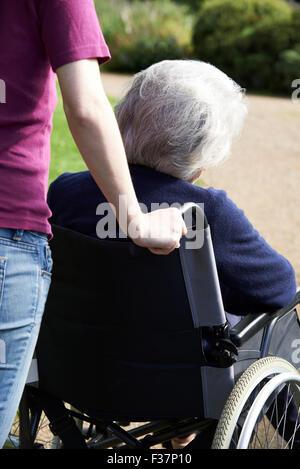 Daughter Pushing Senior Mother In Wheelchair - Stock Photo