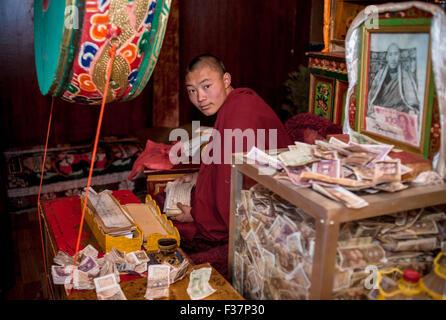 Young Tibetan Monk in Tibet praying at a Temple, Tibet Asia - Stock Photo