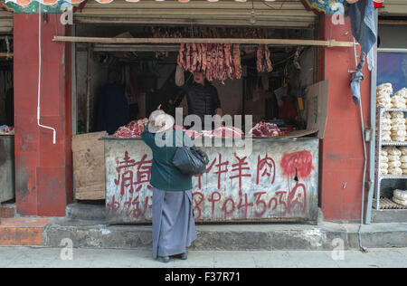 Butchers shop in Lhasa, Tibet. A woman is buying cuts of meat from a butcher in Tibet - Stock Photo