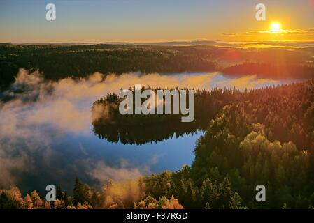 Foggy aerial view of the Aulanko nature reserve park in Finland. The sun hits the fog above the lake in the early - Stock Photo