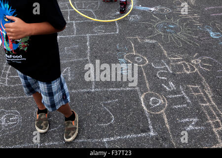 Child chalk drawing on pavement - USA - Stock Photo