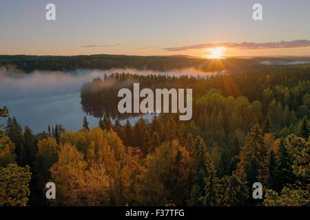 Foggy morning inf the Aulanko nature reserve park in Finland. The sun hits the fog above the lake in the early morning. - Stock Photo