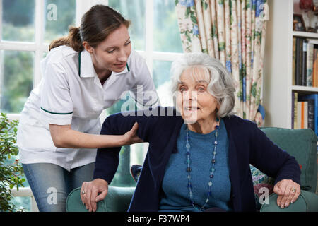 Care Worker Helping Senior Woman To Get Up Out Of Chair - Stock Photo