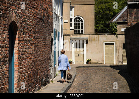 Rear view of lady walking down historic, narrow, cobbled Chapter House Street, (York, England, UK) towards Old Rectory - Stock Photo