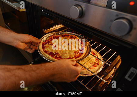 Man hands getting out from the oven a ready homemade pizza. - Stock Photo