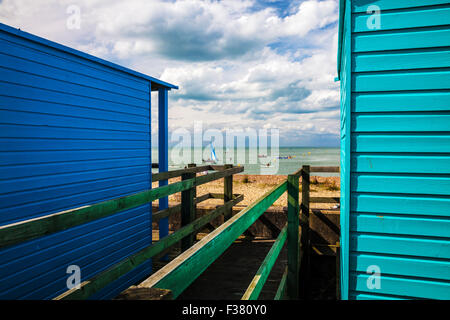 View between wooden beach huts in the Kentish coastal resort of Whitstable. - Stock Photo