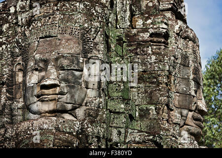 Carved stone giant faces at Bayon temple. Angkor Archaeological Park, Siem Reap Province, Cambodia. - Stock Photo
