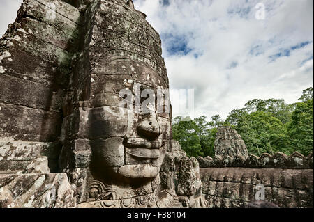 Carved stone giant face at Bayon temple in Angkor Thom. Angkor Archaeological Park, Siem Reap Province, Cambodia. - Stock Photo