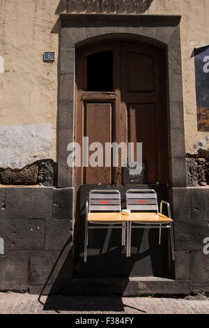 Curious smoking area in a back street outside a bar, with two chairs suspended on a doorway and a board across as - Stock Photo