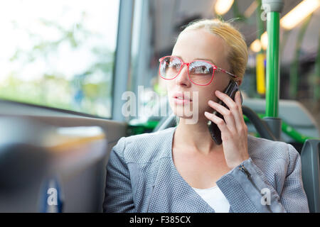 Blonde caucasian business woman talking on cell phone, traveling by bus. Public transport and commuting to work. - Stock Photo