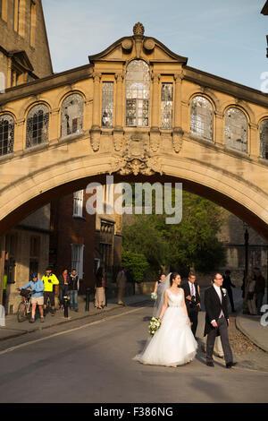 Wedding couple walk beneath Hertford Bridge, popularly known as the Bridge of Sighs, New College Lane, Oxford, Oxfordshire, - Stock Photo