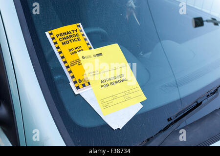 Illegal parking: Parking ticket or Penalty Charge notice with Authorised For Removal notice added on a windscreen, - Stock Photo