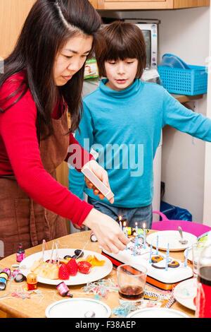Mixed ethnicity boy, Japanese-English, with Japanese mother lighting candles on birthday cake - Stock Photo
