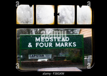 Looking through carriage window at station sign in steam and rain at Medstead & Four Marks station on The Mid Hants - Stock Photo