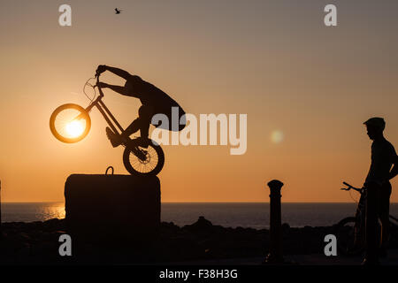 A silhouetted man performing freestyle riding at sunset in Aberystwyth - Stock Photo