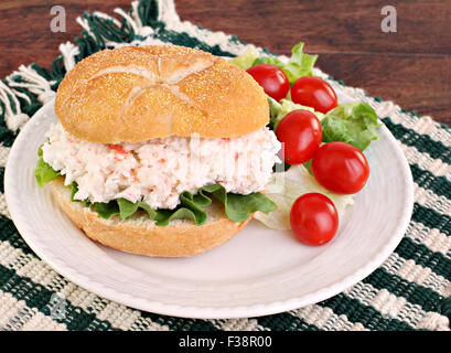 Healthy seafood salad sandwich on a hard roll with a side salad and tomatoes. - Stock Photo