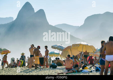 RIO DE JANEIRO, BRAZIL - JANUARY 20, 2013: Locals and visitors crowd Ipanema Beach against the iconic Two Brothers - Stock Photo